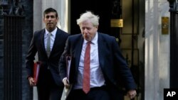 FILE - Britain's Prime Minister Boris Johnson, right, and Finance Minister Rishi Sunak, leave Downing Street to attend a cabinet meeting in London, Sept. 1, 2020.