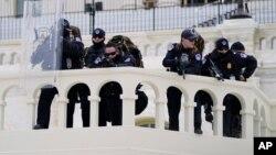 Policajci na položajima motre na demonstrante koji pokušavaju da se probiju kroz policijsku barijeru, 6. januara 2021, na Kapitol hilu, Vašington. (Foto: AP)