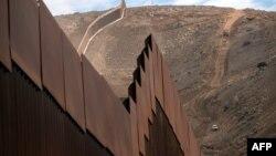 Строительная бригада занимается установкой нового участка стены на границе между США и Мексикой в Эль-Нидо-де-лас-Агилас, штат Нижняя Калифорния, Мексика, 20 января 2021 года