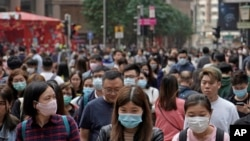 People wear masks on a street in Hong Kong, Friday, Jan. 24, 2020 to celebrate the Lunar New Year which marks the Year of the Rat in the Chinese zodiac. Cutting off access to entire cities with millions of residents to stop a new virus outbreak is a…