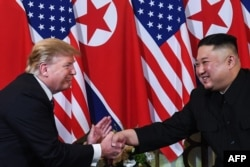 S President Donald Trump (L) shakes hands with North Korea's leader Kim Jong Un following a meeting at the Sofitel Legend Metropole hotel in Hanoi on February 27, 2019. (Photo by Saul LOEB / AFP)