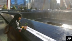 Khudeza Begum traces the name of her slain nephew on the 11th anniversary of the terrorist attacks on the World Trade Center in New York. Begum lost her nephew, Nural Miah, and his wife, Shakila Yasmin, in the attacks on Sept. 11, 2001.