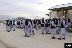 FILE - In this handout photo taken and released on April 11, 2020 by Afghanistan's National Security Council, Taliban prisoners stand before being released from the Bagram prison next to the US military base in Bagram, some 50 km north of Kabul.