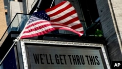 "In this April 6, 2020 photo, a sign at The Anthem music venue reads ""We'll Get Thru This"" at the wharf which is almost completely empty because of the coronavirus outbreak in Washington."