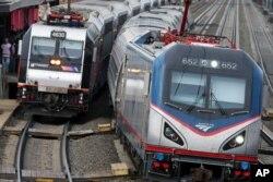 Kereta Amtrak melewati kereta New Jersey Transit yang berhenti untuk menurunkan dan menaikkan penumpang di stasiun kereta Elizabeth di Elizabeth, N.J., di sepanjang Koridor Timur Laut Amtrak, 12 Maret 2016.(Foto: AP)