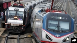 FILE - An Amtrak train passes a New Jersey Transit train stopped to discharge and board passengers at Elizabeth train station in Elizabeth, N.J., along Amtrak's Northeast Corridor, March 12, 2016,