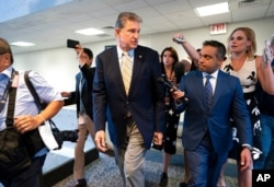 Sen. Joe Manchin, D-W.Va., is followed by reporters after a closed-door meeting on Capitol Hill with other Democrats in the bipartisan talks, in Washington, June 22, 2021.
