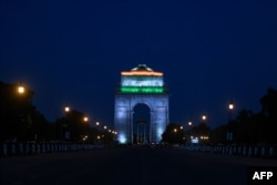 India gate is illuminated with the colors of the Indian national flag as seen from a deserted Rajpath during a government-imposed nationwide lockdown as a preventive measure against the COVID-19 coronavirus in New Delhi on April 8, 2020.