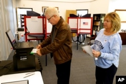 FILE - Greg Froehlinch and his wife Deb of Steubenville, Pa., take advantage of early voting, Sunday, March 15, 2020, in Steubenville, Ohio.