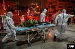 Medical staff members wearing protective clothing to help stop the spread of a deadly virus arrive with a patient at the Wuhan Red Cross Hospital in Wuhan, China, Jan. 25, 2020.