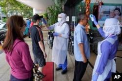 Nurses check the temperatures of visitors as part of the coronavirus screening procedure at a hospital in Kuala Lumpur, Malaysia, Feb. 5, 2020.