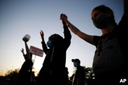 """A demonstrator displays a """"Black Lives Matter"""" sign May 28, 2020, in St. Paul, Minn. Protests over the death of George Floyd, a black man who died in police custody, broke out in the Minneapolis area for a third straight night."""