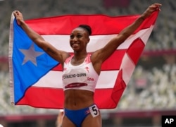 Jasmine Camacho-Quinn, of Puerto Rico celebrates after winning the gold in the women's 100-meters hurdles final at the 2020 Summer Olympics, Aug. 2, 2021, in Tokyo, Japan.