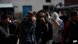Sebagian warga China yang ditangkap atas tuduhan terlibat pencurian siber, menutup wajah mereka saat dibawa ke pengadilan Kathmandu, Nepal, untuk diadili, 24 Desember 2019.