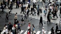 People walk on pedestrian crossings, July 17, 2020, at Tokyo's Shibuya district