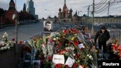 Seorang pria berjalan melewati karangan bunga di lokasi pembunuhan pengkritik Kremlin, Boris Nemtsov. Dia dibunuh pada 27 Februari 2015.