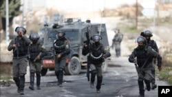 ຕຳຫຼວດຂອງອິສຣາແອລ ແລ່ນເຂົ້າໄປວາງກຳລັງ ໃນລະຫວ່າງການປະທະກັບພວກປະທ້ວງ ຊາວປາແລັສໄຕນ໌ ໃນຂະນະທີ່ ພວກເຂົາປະທ້ວງຕໍ່ຕານ ແຜນການສັນຕິພາບໃນຕາເວັນອອກກາດ ທີ່ໄດ້ປະກາດໃນວັນອັງຄານຜ່ານມາ, ຢູ່ໃກ້ກັບເມືອງຣາມາລາ ໃນ West Bank.