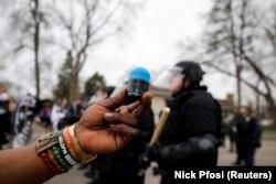 Un manifestant brandit la balle en caoutchouc qui l'a touché au côté lors d'une confrontation avec la police à Brooklyn Center, Minnesota, États-Unis, le 11 avril 2021.