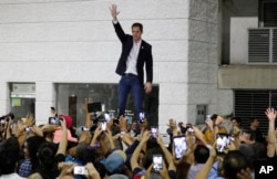 FILE - Opposition leader Juan Guaido waves to supporters during a rally at Bolivar Plaza in Chacao, Venezuela, Feb. 11, 2020.