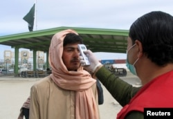 FILE - A health worker takes the temperature of a man, who returned from Afghanistan, following the coronavirus outbreak, outside a medical camp near the Friendship Gate, at the Pakistan-Afghanistan border town of Chaman, Pakistan, Feb. 26. 2020.