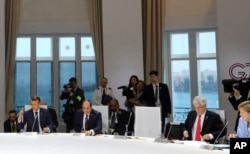 World leaders attend a session on climate change, in Biarritz, France, Aug. 26, 2019, on the third day of the annual G-7 Summit. The empty chair was reserved for U.S. President Donald Trump.