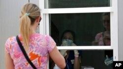 Сотрудница больницы, находясь за окном, дает устные инструкции женщине, которая самостоятельно проводит тест на COVID-19 в Далласе, Техас, 11 июня 2020 года