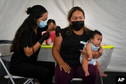 FILE - Laura Sanchez, right, holds her 2-month-old son, Lizandro, while receiving a dose of the Pfizer COVID-19 vaccine at a vaccine clinic set up in the parking lot in Orange, Calif., Aug. 28, 2021.