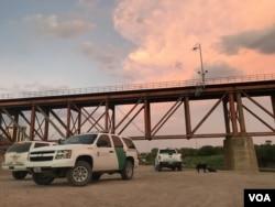 U.S. Border Patrol agents await a detainee transfer under a train bridge in Laredo, Texas, Aug. 6, 2019. (V. Macchi/VOA)