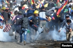 FILE - Coca growers, supporters of former President Evo Morales, run from tear gas as one of them kicks a gas canister during clashes with riot police in Sacaba, on the outskirts of Cochabamba, Bolivia, Nov. 15, 2019.