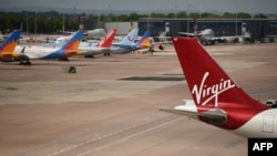 Virgin Atlantic, TUI, and Jet2 aircraft stand near departure gates at Manchester Airport in Manchester, northern England on May 11, 2020,