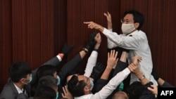 在這幅2020年5月8日拍攝的照片中,泛民主派議員朱凱迪在保安試圖制服他時呼喊。