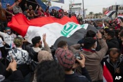 FILE - Anti government protesters carry a big Iraqi flag and chant anti-Iran and anti-U.S. slogans during the ongoing protests in Tahrir Square, Baghdad, Iraq, Jan. 10, 2020.