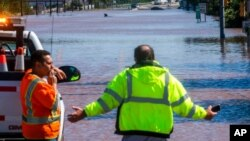 People look at U.S. Route 206, flooded as a result of the remnants of Hurricane Ida, in Somerville, N.J., Sept. 2, 2021.