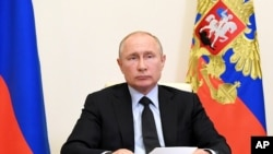 Russian President Vladimir Putin attends a meeting via video conference at the Novo-Ogaryovo residence outside Moscow, Russia, Wednesday, June 10, 2020. Putin held a meeting on IT and telecom industries on Wednesday and urged the government to make…