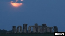 """The full moon, known as the """"Super Flower Moon"""", is seen behind Stonehenge stone circle near Amesbury, Britain, May 26. REUTERS/Peter Cziborra"""