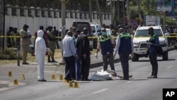 In this image from video, security officers and forensic experts stand near a covered body in a street in Dar es Salaam, Tanzania, Aug. 25, 2021. Four people were killed by a gunman later identified as Hamza Mohamed, a 33-year-old local resident.