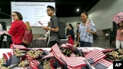 FILE - Immigrants pick flags as they arrive to take their citizenship oath during naturalization ceremonies at a U.S. Citizenship and Immigration Services (USCIS) ceremony in Los Angeles, Sept. 20, 2017.