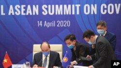 Vietnamese Prime Minister Nguyen Xuan Phuc, left, and his staff prepare documents ahead of the Special ASEAN summit on COVID-19 in Hanoi, Vietnam Tuesday, April 14, 2020. ASEAN leaders and their counterparts from China, Japan and South Korea hold…