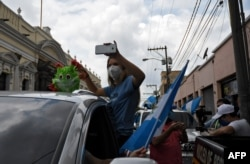 Una mujer participa en una caravana para pedir que el presidente guatemalteco, Alejandro Giammattei, ponga fin a las medidas de confinamiento impuestas desde marzo contra la propagación del nuevo coronavirus. Ciudad de Guatemala 18 de junio de 2020.