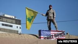 """Участник похорон Касема Сулеймани держит в руках флаг """"Хезболлы"""". Керман, Иран. 7 января 2020 года"""