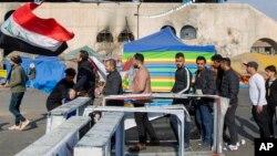 Para pemrotes melewati pos pemeriksaan setibanya di lapangan Tahrir, saat berlangsungnya aksi unjuk rasa di Baghdad, Irak, 25 Desember 2019. (AP Photo/Nasser Nasser)