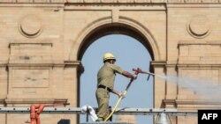 Seorang petugas damkar menyemprotkan cairan disinfektan di Gerbang India saat pemberlakuan karantina nasional untuk mencegah penularan COVID-19 di New Delhi, 17 April 2020. (Foto: AFP)