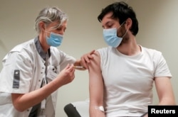 FILE - A volunteer receives a dose of CureVac vaccine or a placebo during a study by the German biotech firm CureVac as part of a testing for a new vaccine against the coronavirus disease (COVID-19), in Brussels, Belgium, March 2, 2021.