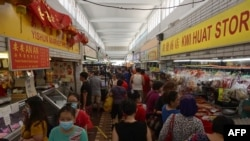 Customers visit a wet market to buy food in Singapore on April 4, 2020, with some people wearing facemasks due to concerns over the spread of the COVID-19 coronavirus.