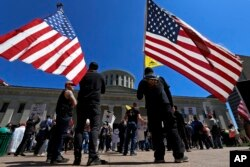 FILE - Anti-lockdown protesters gather outside the Ohio Statehouse in Columbus, Ohio, April 20, 2020.