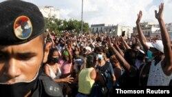 La gente reacciona durante las protestas contra y en apoyo del gobierno, en La Habana, Cuba, el domingo 11 de julio de 2021.