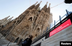 A tourist records with her mobile phone the landmark Sagrada Familia basilica, which stopped receiving visitors due to the coronavirus outbreak in Barcelona, Spain, March 13, 2020.