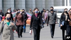 Pedestrians wear face masks to help prevent the spread of the coronavirus, Wednesday, April 1, 2020, in Pyongyang, North Korea. The new coronavirus causes mild or moderate symptoms for most people, but for some, especially older adults and people…