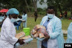 Medical workers distribute food to returnees at the quaratine facility in Blantyre, Jan. 11, 2021. (Lameck Masina/VOA)