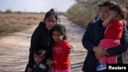 Dos solicitantes de asilo guatemaltecas con sus hijos esperan por transportación tras cruzar el Río Grande desde México a Texas, EE. UU., en una balsa el 10 de marzo de 2021.